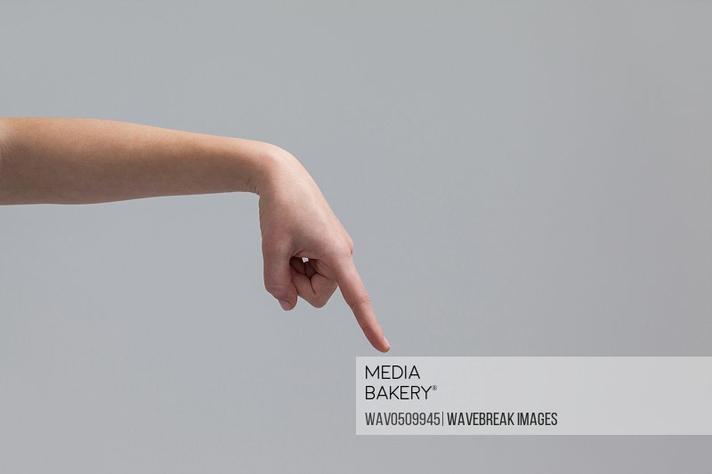 Hand of a woman pointing downwards against grey background