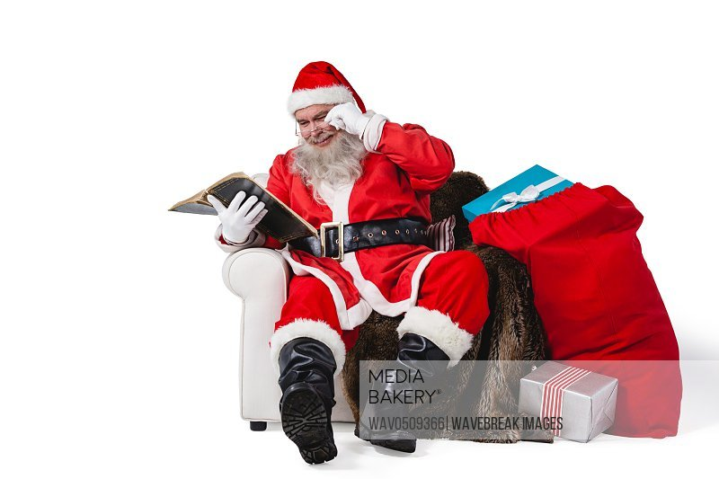 Santa reading bible with sack of christmas present beside him