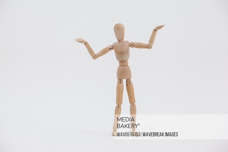 Wooden figurine standing with arms spread against white background