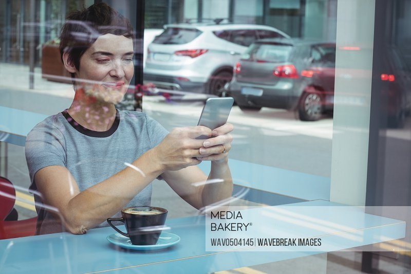 Businesswoman using mobile phone while having coffee in office