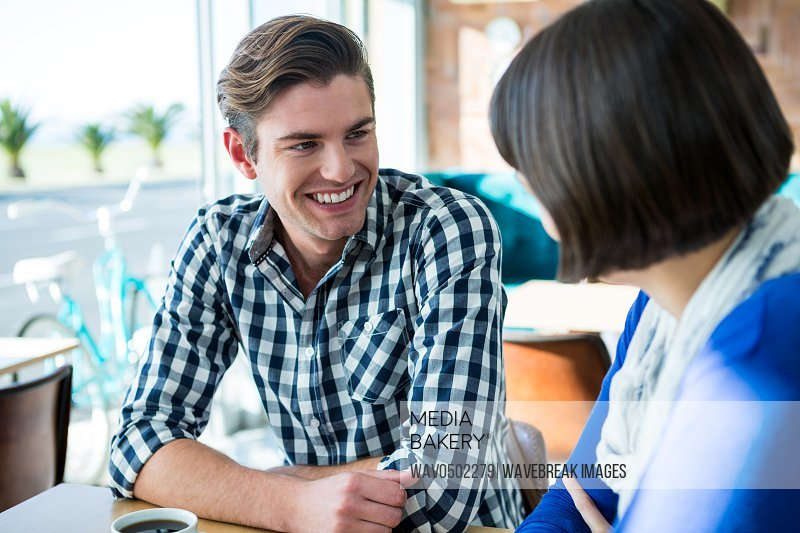 Smiling couple talking to each other in coffee shop