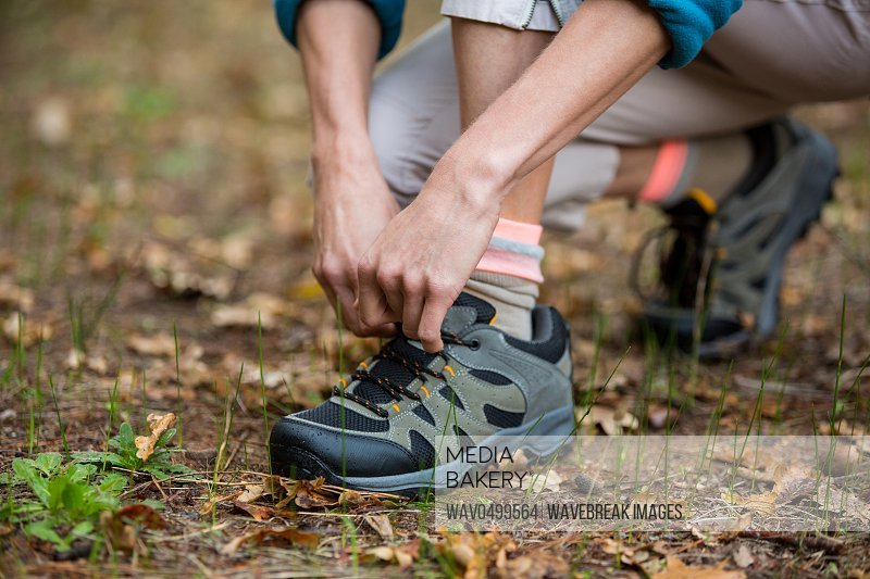 Female hiker tying shoelaces outdoors in forest