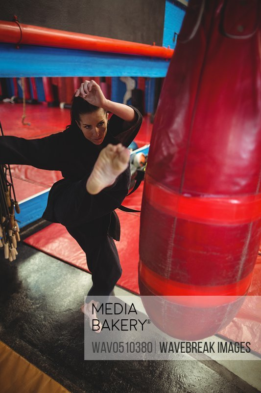 Female karate player boxer practicing boxing with punching bag in fitness studio