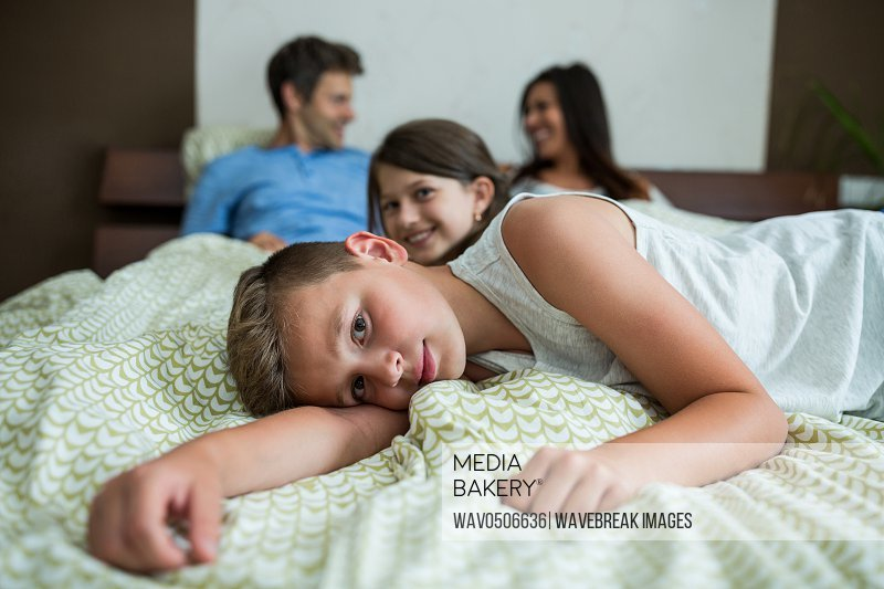 Family lying on bed in bedroom at home