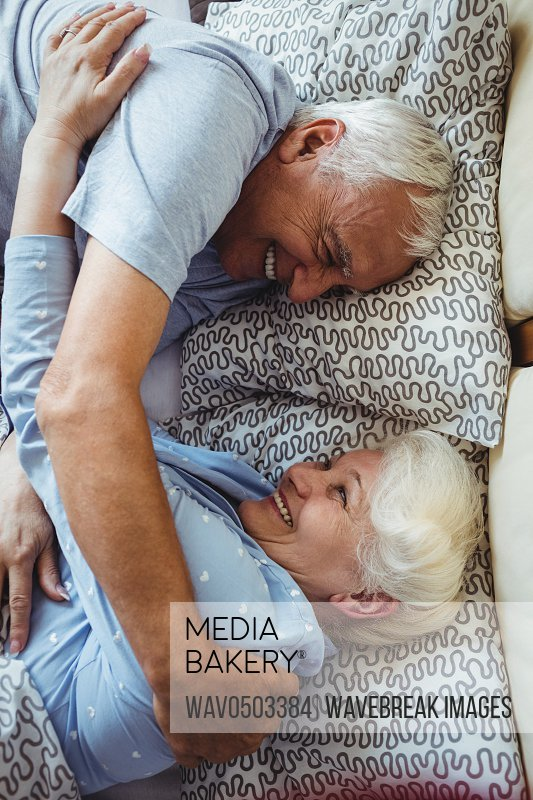 Senior couple embracing on bed in bedroom