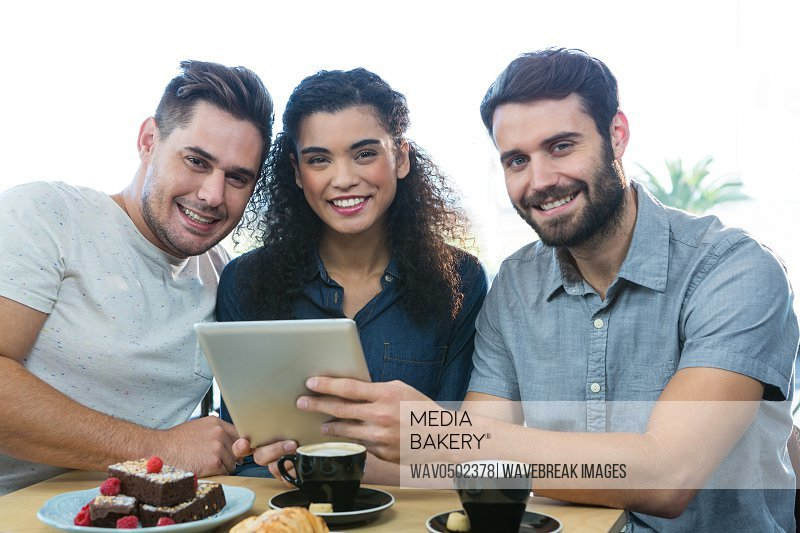 Portrait of Three smiling friends using a digital tablet in coffee shop