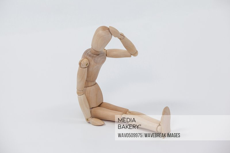 Tensed wooden figurine sitting with hand on head against white background