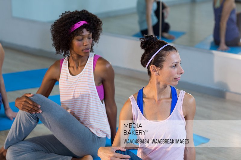 Two women performing yoga in gym