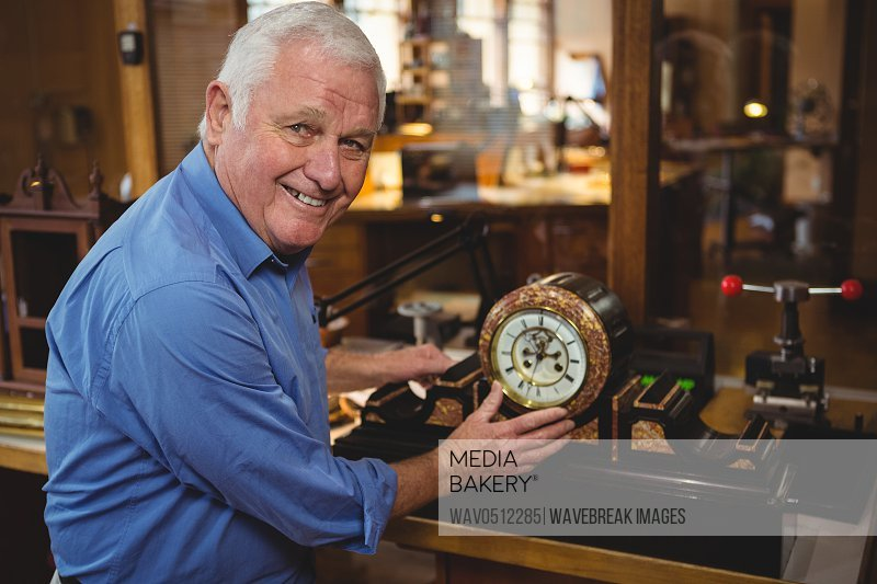 Portrait of horologist checking a clock in workshop
