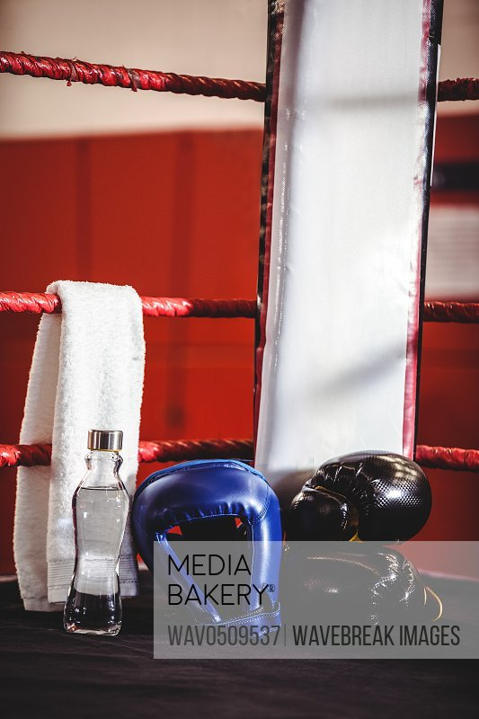 Boxing gloves, headgear, water bottle and a towel in a corner of boxing ring