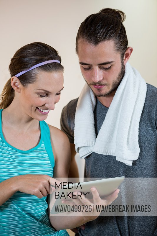 Smiling fitness trainer and woman using digital tablet in fitness studio