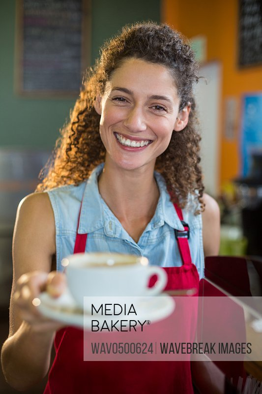 Portrait of smiling female staff serving a cup of coffee at coffee shop