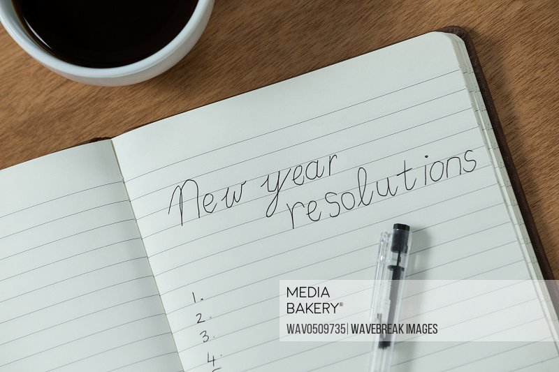 New year resolutions written on diary with coffee mug on wooden table