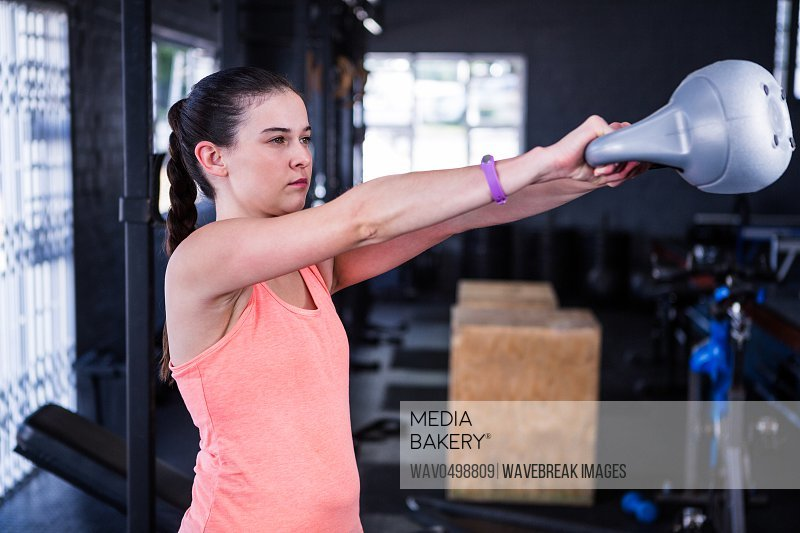 Female athlete holding kettlebell while standing in gym