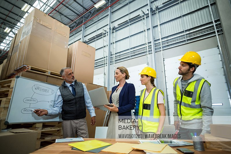 Warehouse workers and manager discussing plan on whiteboard in warehouse