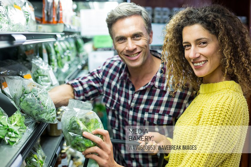 Portrait of happy couple selecting vegetables in organic section of supermarket