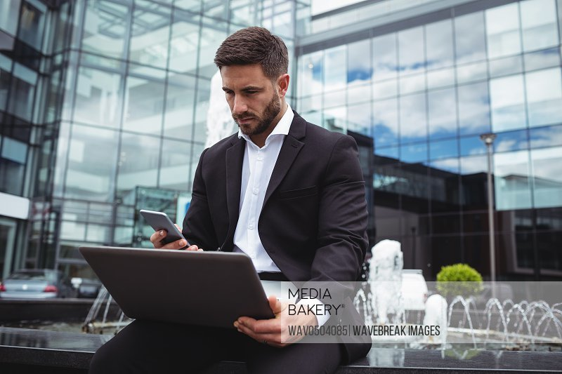 Businessman using mobile phone and laptop in office building