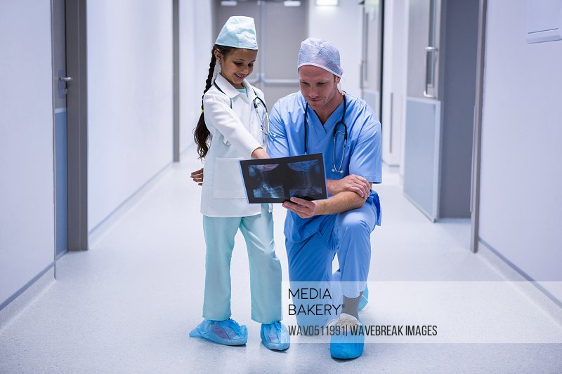 Smiling girl and doctor looking at x-ray in corridor at hospital