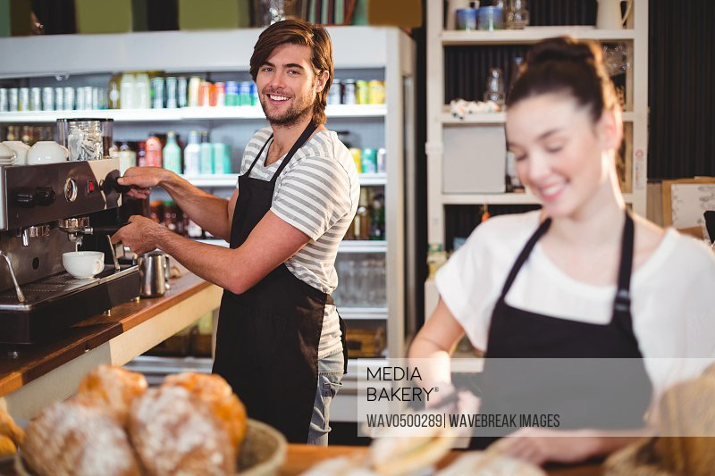 Waiter and waitress working behind the counter in cafe