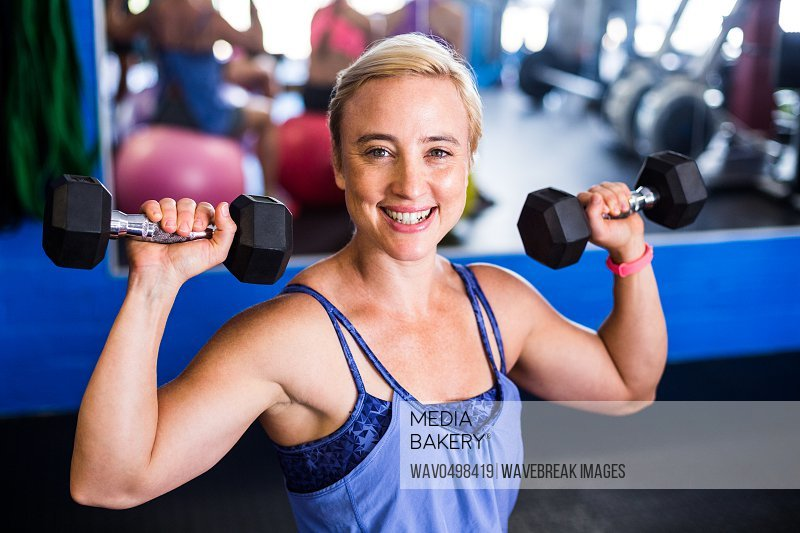 Portrait of happy woman lifting dumbbell while exercising in gym