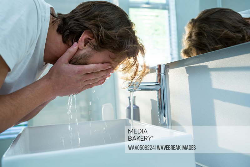 Man washing his face with water in bathroom at home