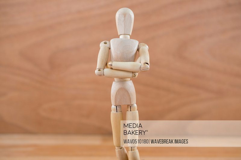 Close-up of wooden figurine standing with arms crossed