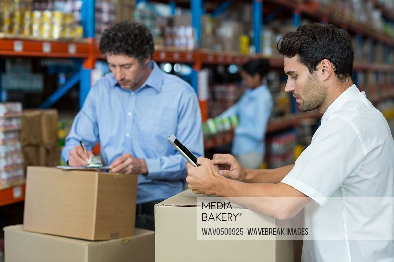 Two warehouse workers working together in warehouse