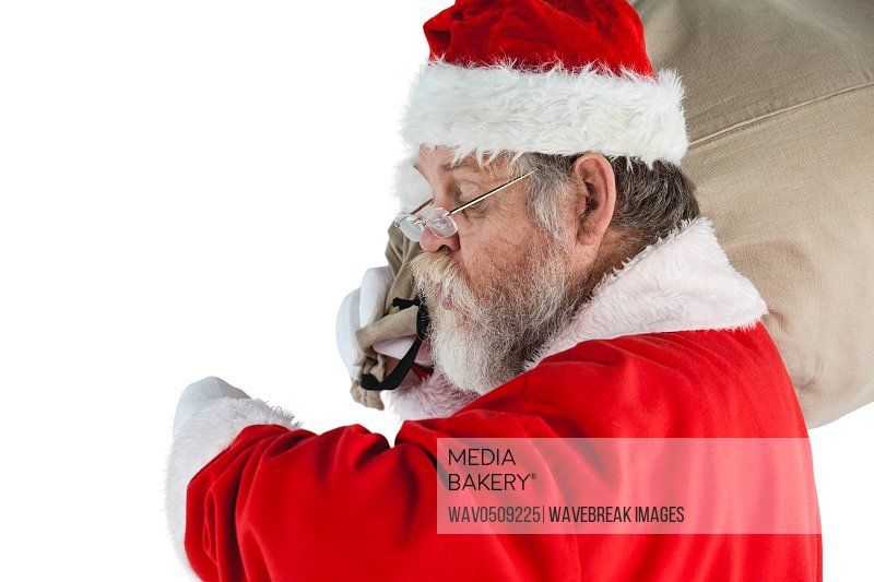 Santa claus looking at wristwatch while holding sack full of gifts