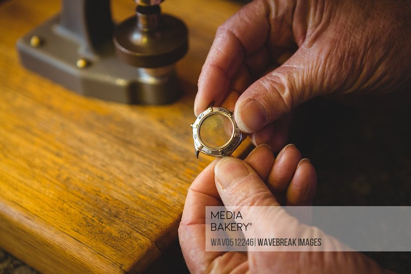 Close-up of horologist holding watch frame in workshop