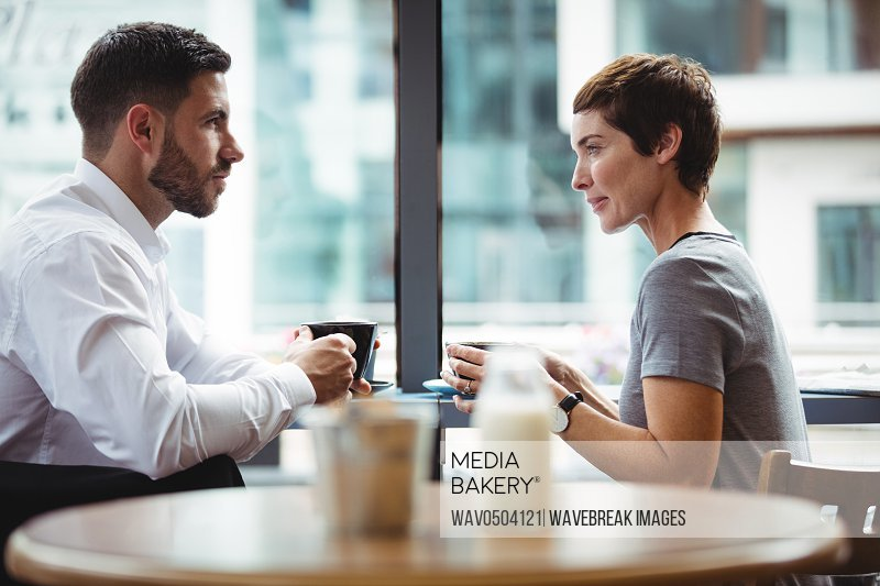 Businesspeople interacting while having coffee in office