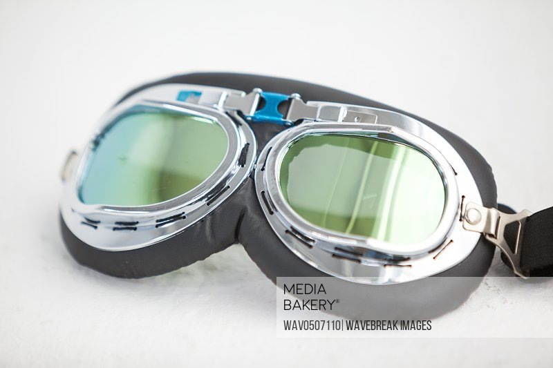 Close-up of aviator goggles against white background