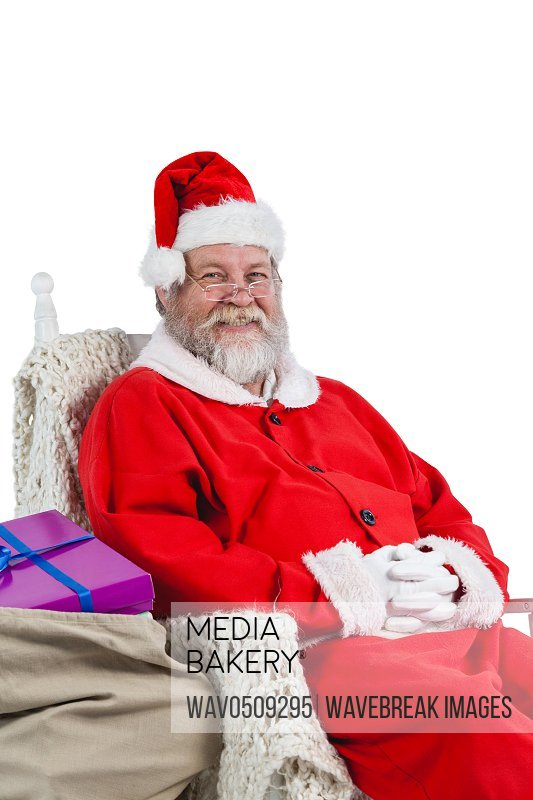 Santa claus sitting on chair with sack of christmas present beside him