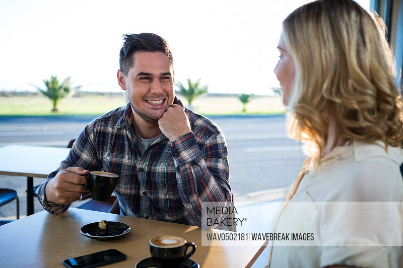 Smiling couple interacting with each other while having cup of coffee in cafeteria
