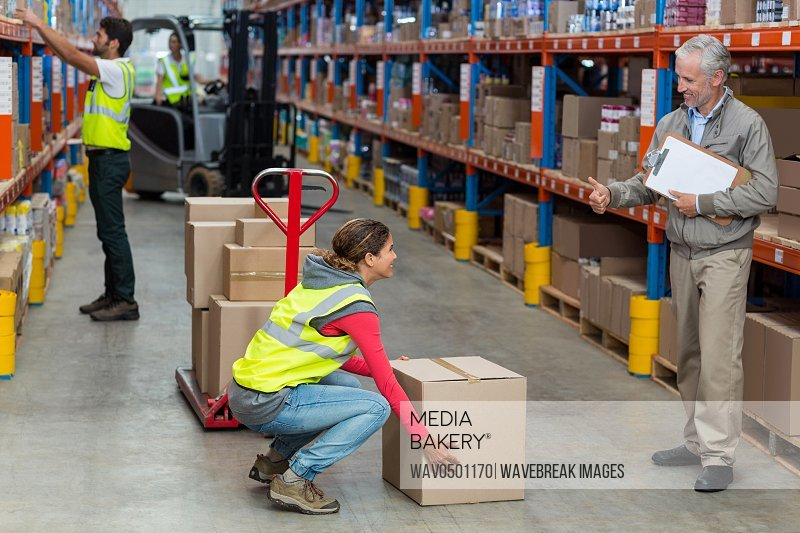 Warehouse manager showing thumbs up to female worker while carrying cardboard boxes in warehouse