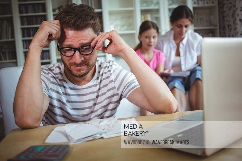 Worried man sitting at table with bills and laptop while his wife and daughter sitting on sofa