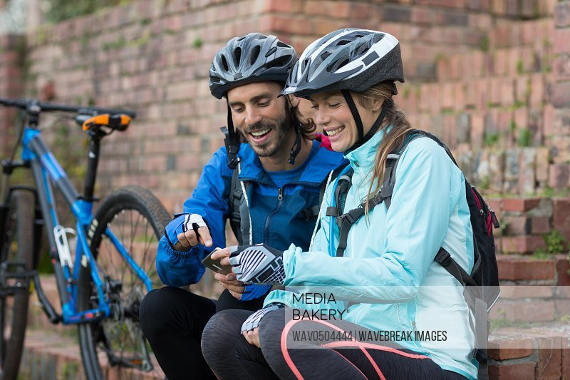 Biker couple using mobile phone in countryside
