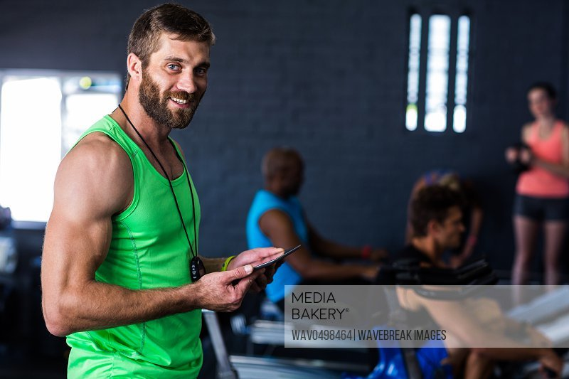 Portrait of smiling hipster holding tablet while standing in gym