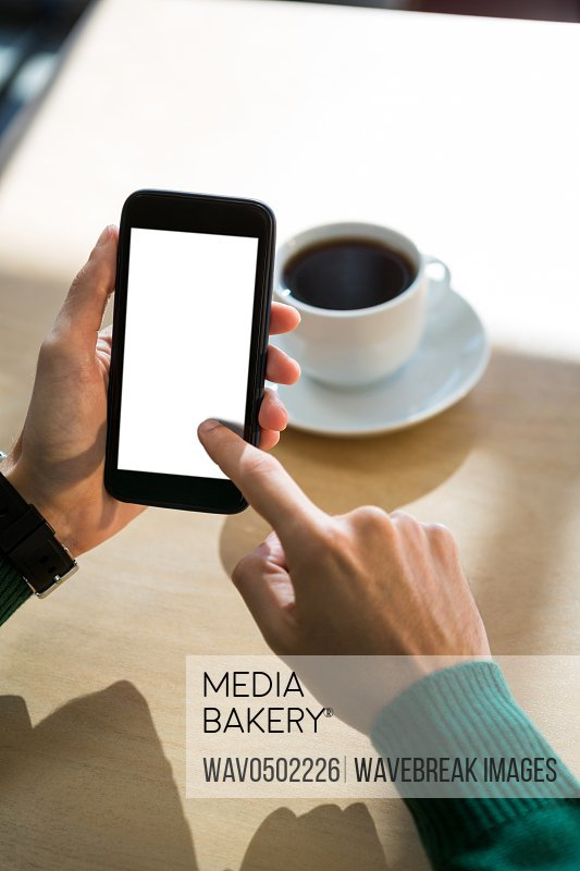 Hand using mobile phone with cup of coffee in table in cafeteria