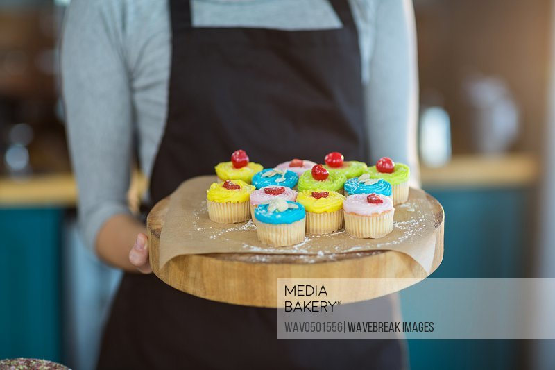 Mid-section of waitress holding cup cake on tray in cafA?