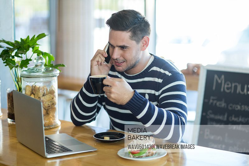 Smiling man talking on mobile phone while having coffee in cafA?