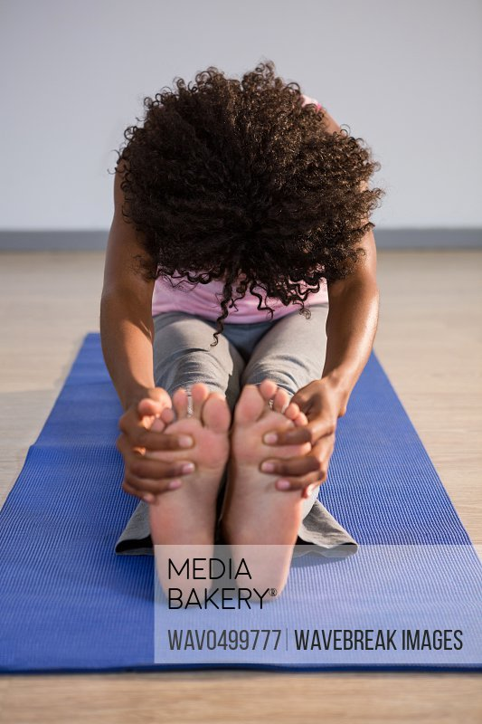 Woman doing seated forward bend on exercise mat in fitness studio