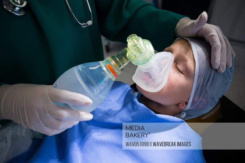 Surgeon placing oxygen mask on patient mouth in operation theater