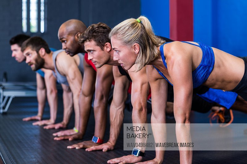 People doing push-ups while exercising in gym