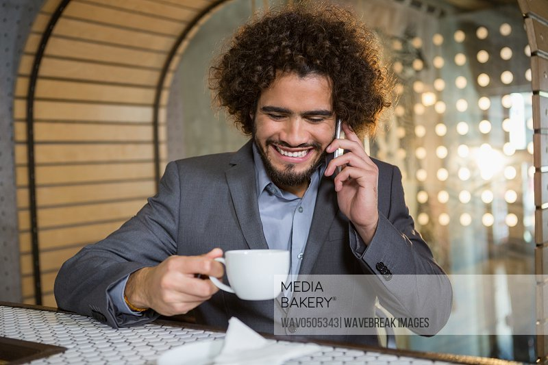 Businessman talking on mobile phone while having cup of tea in bar