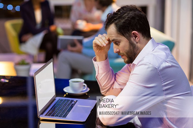 Thoughtful businessman working on laptop in office at night