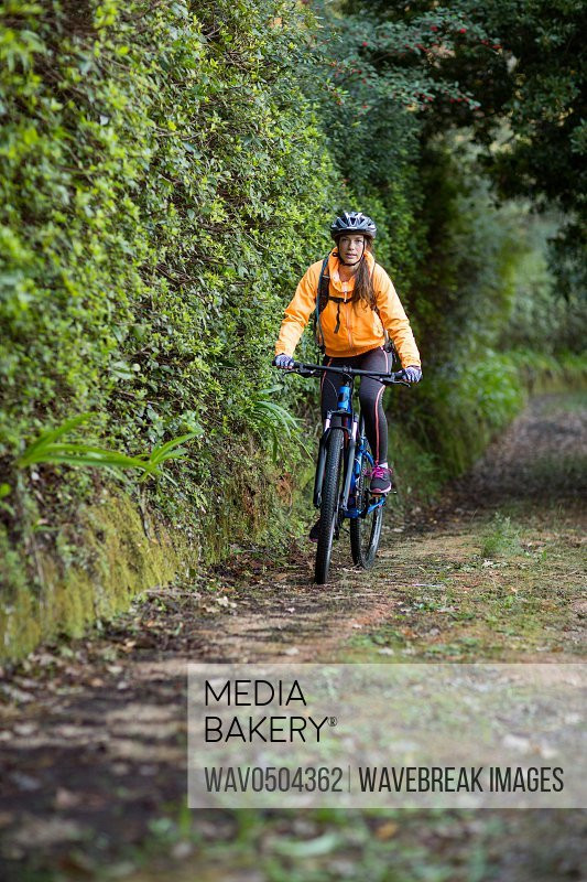 Female biker cycling in countryside forest