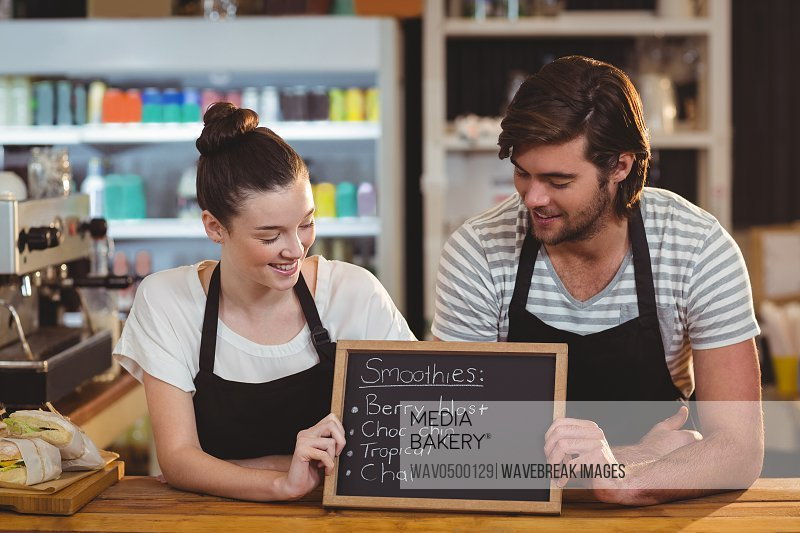 Waiter and waitress holding chalkboard at counter in cafe