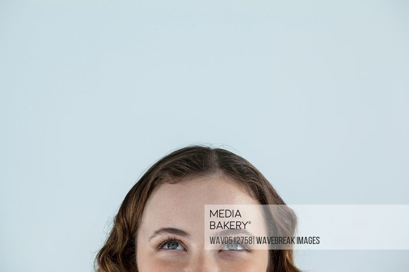 Close-up of beautiful woman looking upward against grey background