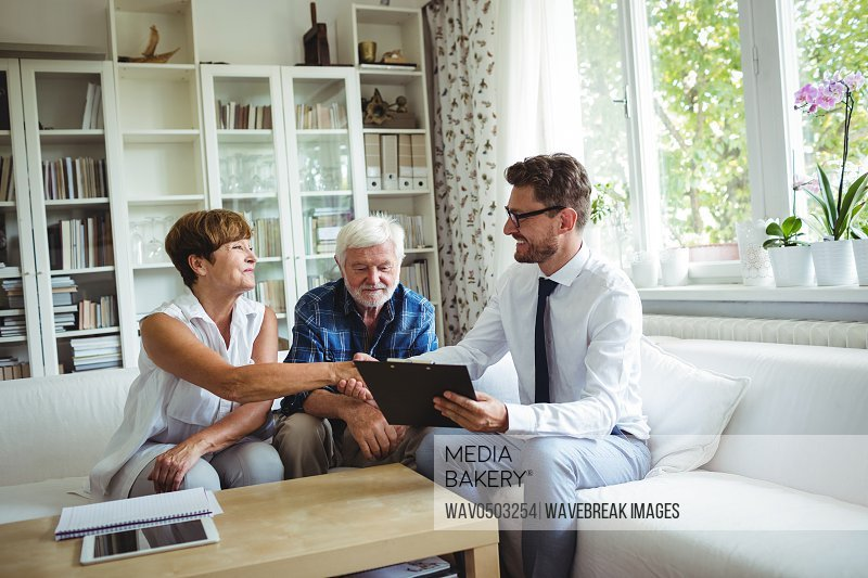 Financial advisor shaking hands with senior woman in living room