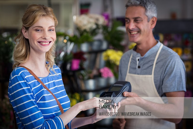 Portrait of smiling woman making payment with her credit card to florist in the shop